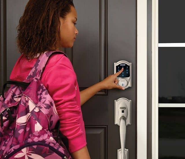 image of a young woman using a Schlage smart lock on her home's front door